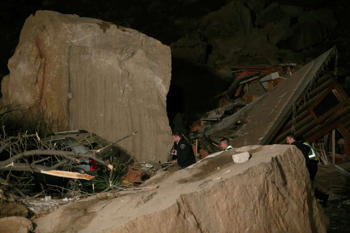 Law enforcement officers search through the rubble of a two-story log home that was crushed by boulders that broke loose from the cliff above it and killed two people inside the home Thursday, Dec. 12, 2013 in Rockville, Utah.