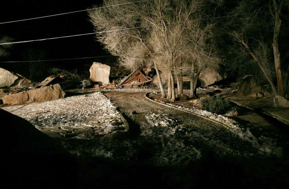 Flood lights from fire engines parked on nearby state Route 9 shine on the rubble of a two-story log home that was crushed by boulders that broke loose from the cliff above it and killed two people inside the home Thursday, Dec. 12, 2013 in Rockville, Utah. Photo: Jud Burkett / The Spectrum & Daily News, AP / THE SPECTRUM & DAILY NEWS