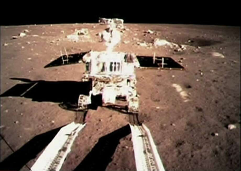 "In this image taken by the on-board camera of the lunar probe Chang'e-3 and made off the screen of the Beijing Aerospace Control Center in Beijing, China's first moon rover ""Jade Rabbit"" touches the lunar surface Sunday, Dec. 15, 2013. ""Jade Rabbit"" touched down on the moon and left deep traces on its loose soil, state media reported Sunday, several hours after the country successfully carried out the world's first soft landing of a space probe on the moon in nearly four decades. (AP Photo/Xinhua)  Photo: AP / Xinhua"