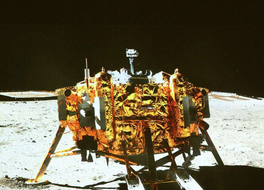 In this image made off the screen at the Beijing Aerospace Control Center in Beijing, is the Chang'e-3 moon lander, taken by the camera on the 'Yutu'  (Jade Rabbit) moon rover,  during the mutual-photograph process in the area known as Sinus Iridum (Bay of Rainbows), Sunday, Dec. 15, 2013.  Yutu touched down on the moon and left deep traces on its loose soil, state media reported Sunday, several hours after the country successfully carried out the world's first soft landing of a space probe on the moon in nearly four decades. (AP Photo / Wang Jianmin,  Xinhua)  Photo: Wang Jianmin, AP / Xinhua