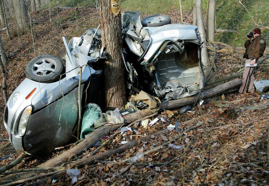 Deputy Aaron Gilman of the Tippecanoe County Sheriff's Office photographs the mangled wreckage of a Hyundai following a one-vehicle crash Friday, Dec.  13, 2013, near off Old Ind. 25 near Lafayette, Ind. It took firefighters nearly two hours to free a man from the car that was wrapped around a tree in a ravine. The man was airlifted to an Indianapolis hospital. Photo: John Terhune, AP / AP2013