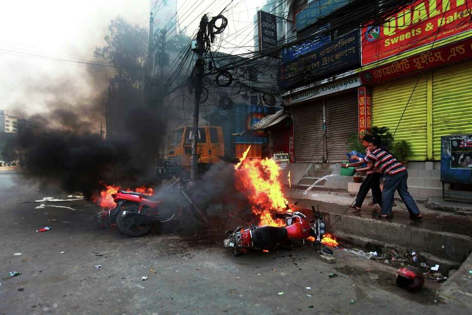 Bangladeshi men try to douse burning vehicles after they were set on fire by activists of Islamist party, Jamaat-e-Islami, following the execution of their party leader Abdul Quader Mollah in Dhaka, Bangladesh, Friday, Dec. 13, 2013. The execution of the opposition leader in Bangladesh sparked violent protests Friday as activists torched homes and businesses belonging to government supporters, leaving at least three people dead, in a fresh wave of bloodshed ahead of elections next month. Photo: Suvra Kanti Das, AP / AP2013
