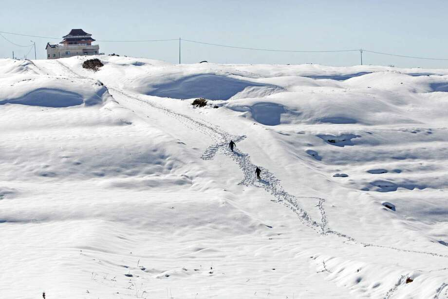 A Palestinian walks on snow to reach their homes in the West Bank city of Nablus, Sunday, Dec. 15, 2013. The Gaza Strip received its first shipment of industrial fuel in 45 days Sunday. A lack of fuel has hampered rescue efforts in Gaza, where thousands of residents fled flooded homes. The storm let up Saturday, but authorities in the region still struggled to clear roads and repair downed power lines. Photo: Nasser Ishtayeh, AP / THE ASSOCIATED PRESS2013