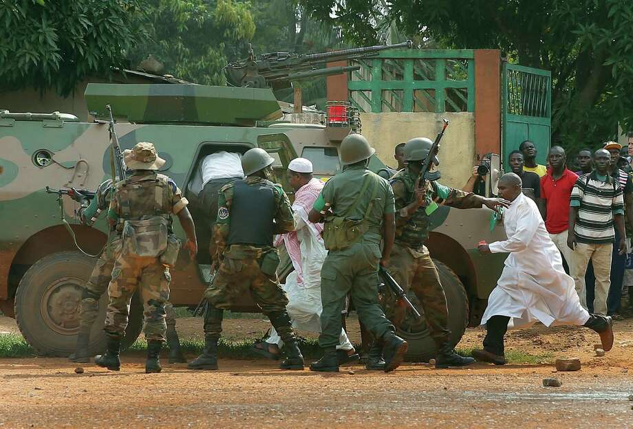 FOMAC troops, regional peacekeepers, evacuate Muslim clerics under a hail of fire from the St Jacques Church in Bangui, Central African Republic, Thursday Dec. 12, 2013. An angry crowd had gathered outside the church following rumors that a Seleka general was inside.  More than 500 people have been killed over the past week in sectarian fighting in Central African Republic. Photo: Jerome Delay, AP / AP2013