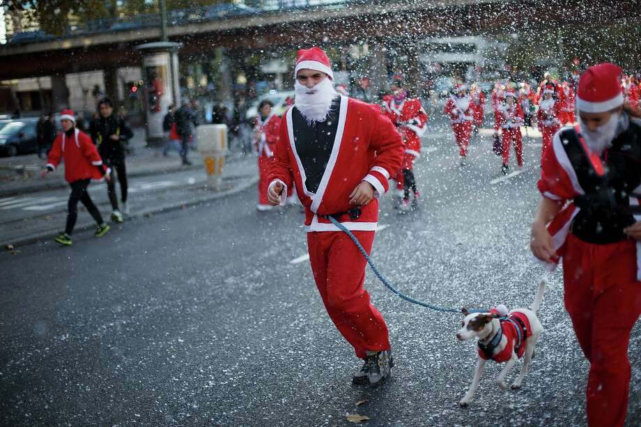 A participant runs with his dog along Castellana Street during the Santa Claus or 'Papa Noel' race on December 14, 2013 in Madrid, Spain. An estimated 6,000 adults dressed as Santa Claus and children dressed as elves turned out to take part in the 5.5 kilometer race to kick off Madrid's Christmas festivities. One Euro per participant will be donated to a charity that distributes presents to deprived children around the world by the event's organizers. Photo: Pablo Blazquez Dominguez, Getty Images / 2013 Pablo Blazquez Dominguez