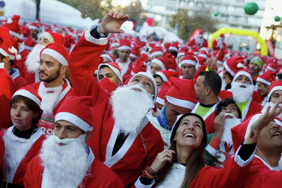 Participants wait for the start of the Santa Claus or 'Papa Noel' race on December 14, 2013 in Madrid, Spain. An estimated 6,000 adults dressed as Santa Claus and children dressed as elves turned out to take part in the 5.5 kilometer race to kick off Madrid's Christmas festivities. One Euro per participant will be donated to a charity that distributes presents to deprived children around the world by the event's organizers. Photo: Pablo Blazquez Dominguez, Getty Images / 2013 Pablo Blazquez Dominguez