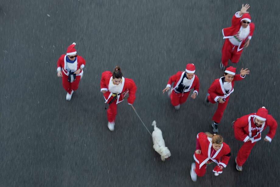 A participant runs with her dog along Castellana Street during the Santa Claus or 'Papa Noel' race on December 14, 2013 in Madrid, Spain. An estimated 6,000 adults dressed as Santa Claus and children dressed as elves turned out to take part in the 5.5 kilometer race to kick off Madrid's Christmas festivities. One Euro per participant will be donated to a charity that distributes presents to deprived children around the world by the event's organisizers. Photo: Pablo Blazquez Dominguez, Getty Images / 2013 Pablo Blazquez Dominguez
