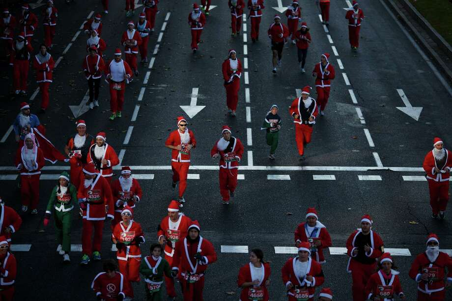 Participants run along Castellana Street during the Santa Claus or 'Papa Noel' race on December 14, 2013 in Madrid, Spain. An estimated 6,000 adults dressed as Santa Claus and children dressed as elves turned out to take part in the 5.5 kilometer race to kick off Madrid's Christmas festivities. One Euro per participant will be donated to a charity that distributes presents to deprived children around the world by the event's organisizers. Photo: Pablo Blazquez Dominguez, Getty Images / 2013 Pablo Blazquez Dominguez