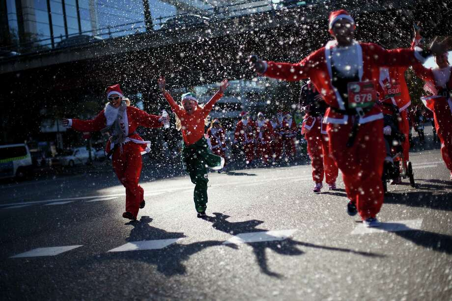 Participants run along Castellana Street during the Santa Claus or 'Papa Noel' race on December 14, 2013 in Madrid, Spain. An estimated 6,000 adults dressed as Santa Claus and children dressed as elves turned out to take part in the 5.5 kilometer race to kick off Madrid's Christmas festivities. One Euro per participant will be donated to a charity that distributes presents to deprived children around the world by the event's organizers. Photo: Pablo Blazquez Dominguez, Getty Images / 2013 Pablo Blazquez Dominguez