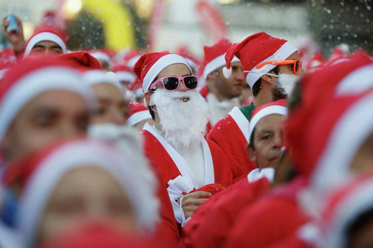 Participants wait for the start of the Santa Claus or 'Papa Noel' race on December 14, 2013 in Madrid, Spain. An estimated 6,000 adults dressed as Santa Claus and children dressed as elves turned out to take part in the 5.5 kilometer race to kick off Madrid's Christmas festivities. One Euro per participant will be donated to a charity that distributes presents to deprived children around the world by the event's organizers.