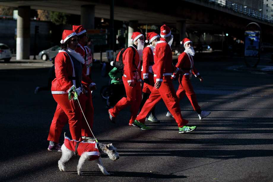 A participant walks with her dog along Castellana Street during the Santa Claus or 'Papa Noel' race on December 14, 2013 in Madrid, Spain. An estimated 6,000 adults dressed as Santa Claus and children dressed as elves turned out to take part in the 5.5 kilometer race to kick off Madrid's Christmas festivities. One Euro per participant will be donated to a charity that distributes presents to deprived children around the world by the event's organizers. Photo: Pablo Blazquez Dominguez, Getty Images / 2013 Pablo Blazquez Dominguez