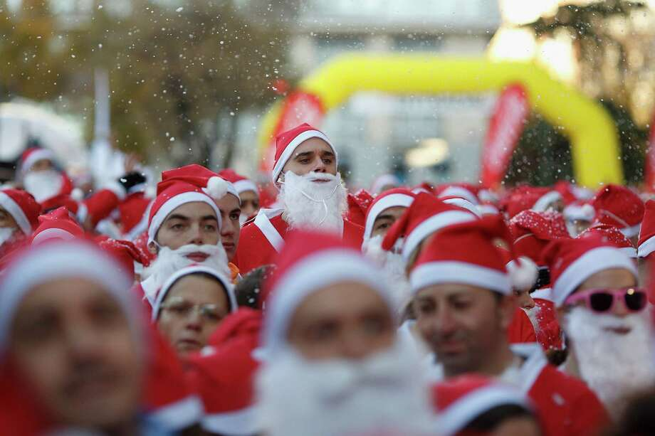 Participants warm up before the start of the Santa Claus or 'Papa Noel' race on December 14, 2013 in Madrid, Spain. An estimated 6,000 adults dressed as Santa Claus and children dressed as elves turned out to take part in the 5.5 kilometer race to kick off Madrid's Christmas festivities. One Euro per participant will be donated to a charity that distributes presents to deprived children around the world by the event's organizers. Photo: Pablo Blazquez Dominguez, Getty Images / 2013 Pablo Blazquez Dominguez