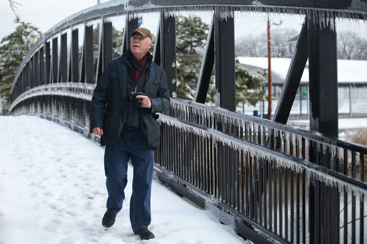 John Marozsan, of Chicago, watches a bird in the ice covered trees on the bridge in Milford on Sunday, Dec. 15, 2013. Marozsan was in Milford visiting his son, Andre, for the holidays.