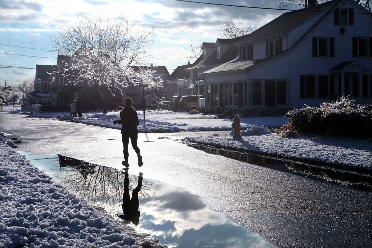 A jogger is reflected in a puddle on Seaview Ave. in Milford on Sunday, Dec. 15, 2013.