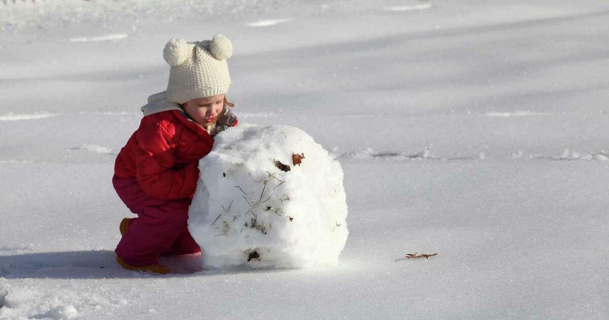 Elle Naumann, 2, of Milford, rolls a snowball behind Jonathan Law High School in Milford on Sunday, Dec. 15, 2013.