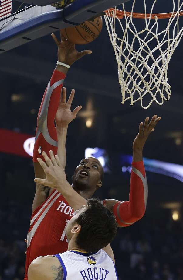 Dwight Howard, back, shoots over Andrew Bogut. Photo: Ben Margot, Associated Press