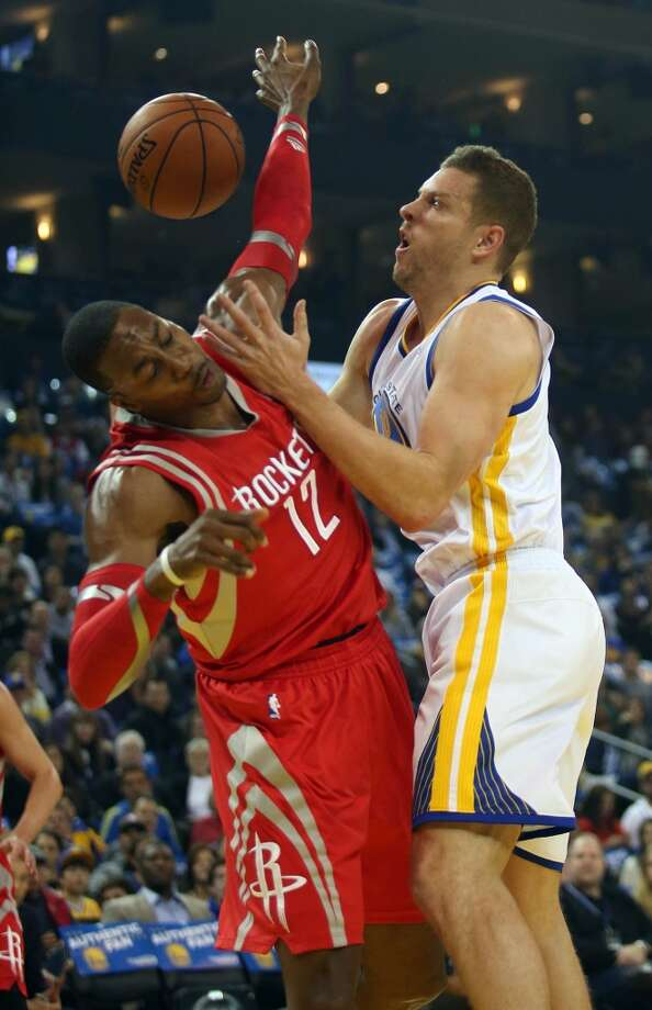 David Lee gets tangled up with the Dwight Howard (12) as they fight for a rebound. Photo: JANE TYSKA, McClatchy-Tribune News Service