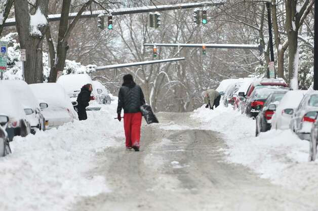 People work to shovel snow out from around their cars in downtown Albany on Sunday, Dec. 15, 2013 in Albany, NY.   (Paul Buckowski / Times Union) Photo: PAUL BUCKOWSKI / 00025049A