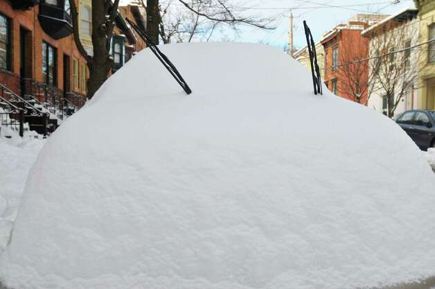 Wipers stick out from the covering of snow on a car parked on Chestnut St. on Sunday, Dec. 15, 2013 in Albany, NY.   (Paul Buckowski / Times Union) Photo: PAUL BUCKOWSKI / 00025049A