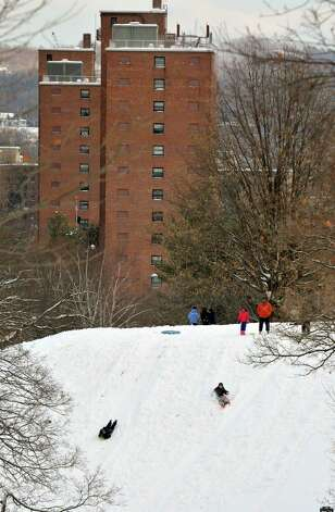 Children slide down a hill in Lincoln Park on Sunday, Dec. 15, 2013 in Albany, NY.   (Paul Buckowski / Times Union) Photo: PAUL BUCKOWSKI / 00025049A