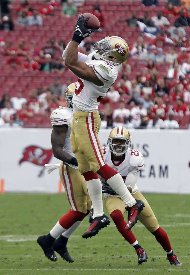 San Francisco 49ers free safety Eric Reid (35) intercepts a pass by Tampa Bay Buccaneers quarterback Mike Glennon during the fourth quarter of an NFL football game, Sunday, Dec. 15, 2013, in Tampa, Fla. The 49ers defeated the Buccaneers 33-14. Looking on is teammate Carlos Rogers (22). (AP Photo/Chris O'Meara) Photo: Chris O'Meara, Associated Press