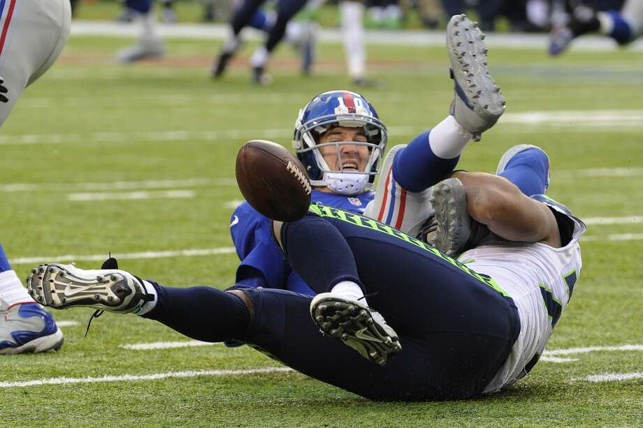 Seattle Seahawks defensive end Michael Bennett, bottom, forces a fumble off New York Giants quarterback Eli Manning  during the second half of an NFL football game on Sunday, Dec. 15, 2013, in East Rutherford, N.J. The Giants recovered their fumble on the play. (AP Photo/Bill Kostroun) Photo: Bill Kostroun, ASSOCIATED PRESS