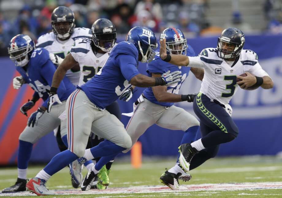 Seattle Seahawks quarterback Russell Wilson (3) stiff-arms New York Giants defensive end Justin Tuck (91) during the second half of an NFL football game on Sunday, Dec. 15, 2013, in East Rutherford, N.J. (AP Photo/Kathy Willens) Photo: Kathy Willens, ASSOCIATED PRESS