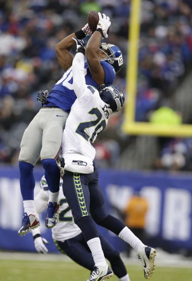 New York Giants wide receiver Victor Cruz, left, makes a catch as Seattle Seahawks cornerback Jeremy Lane defends on the play during the second half of an NFL football game, Sunday, Dec. 15, 2013, in East Rutherford, N.J. Cruz was banged up on the play and left the game with an injury. (AP Photo/Kathy Willens) Photo: Kathy Willens, AP