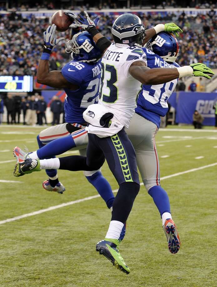 New York Giants strong safety Antrel Rolle, left, intercepts a pass intended for Seattle Seahawks wide receiver Ricardo Lockette, center, as cornerback Trumaine McBride (38) defends on the play during the second half of an NFL football game, Sunday, Dec. 15, 2013, in East Rutherford, N.J. (AP Photo/Bill Kostroun) Photo: Bill Kostroun, AP