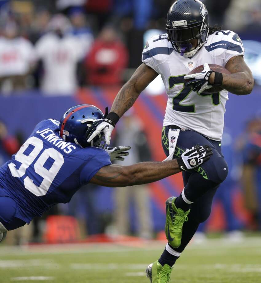 Seattle Seahawks running back Marshawn Lynch (24) avoids the tackle attempt of New York Giants defensive tackle Cullen Jenkins (99) during the second half of an NFL football game, Sunday, Dec. 15, 2013, in East Rutherford, N.J. (AP Photo/Kathy Willens) Photo: Kathy Willens, AP