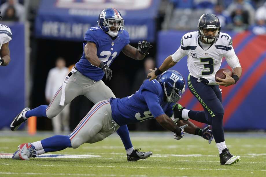 Seattle Seahawks quarterback Russell Wilson (3) gets pass the tackle attempt of  New York Giants defensive end Justin Tuck (91) during the second half of an NFL football game, Sunday, Dec. 15, 2013, in East Rutherford, N.J. (AP Photo/Kathy Willens) Photo: Kathy Willens, AP