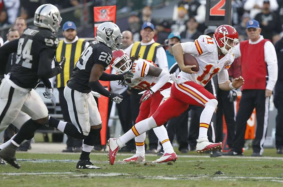 Alex Smith, who had a quarterback rating of 158.3, eludes the Raiders' Brandian Ross. Photo: Michael Macor, The Chronicle