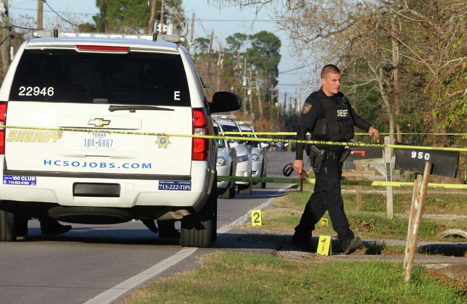 A Harris County Sheriff's Office Deputy walks by evidence laying on a shooting scene on East Harris County where four young males were shot, Sunday, Dec. 15, 2013. The shooting is still under investigation. Photo: Marie D. De Jesús, Houston Chronicle / © 2013 Houston Chronicle