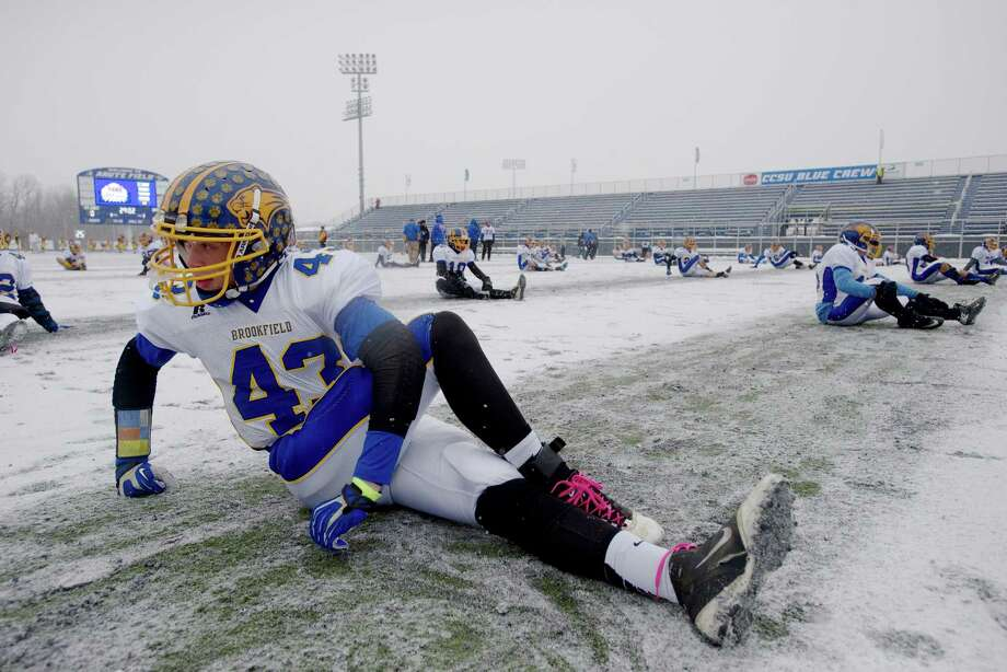 With frigid temperatures and a snow-covered field, the conditions were less than ideal for running and throwing the ball Photo: H John Voorhees III / The News-Times Freelance