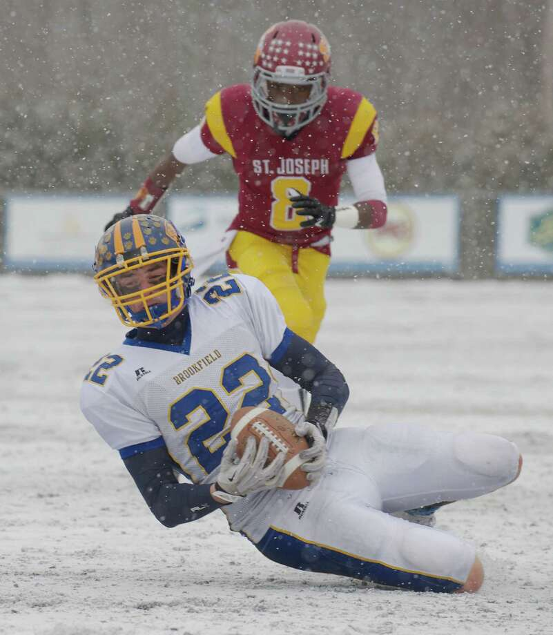 Brookfield's Liam Clancy (22) catches a pass in front of St Joseph's Darren Jackson (8) during the Class M football championship game between Brookfield and St Joseph high schools at Central Connecticut State University's Arute Field in New Britain, Conn, on Saturday, December 14, 2013. St Joseph's beat Brookfield, 54-14. Photo: H John Voorhees III / The News-Times Freelance