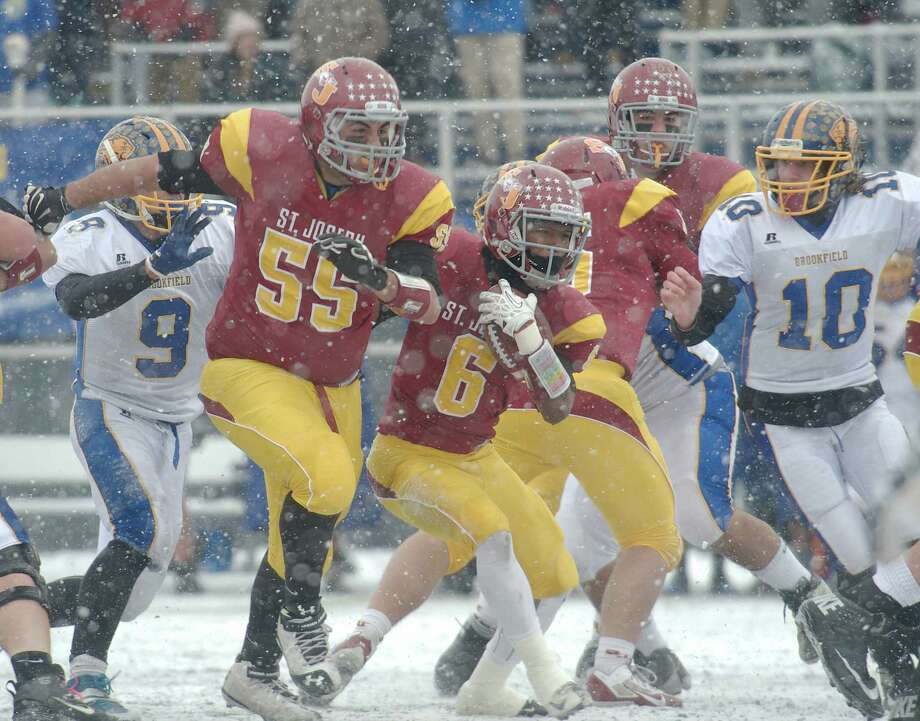 St Joseph's Mufasha Abdul Basir (6) cuts past lineman Troy Vazzano (55) during the Class M football championship game between Brookfield and St Joseph high schools at Central Connecticut State University's Arute Field in New Britain, Conn, on Saturday, December 14, 2013. Brookfield's Peter Manesis (10) moves in. Photo: H John Voorhees III / The News-Times Freelance