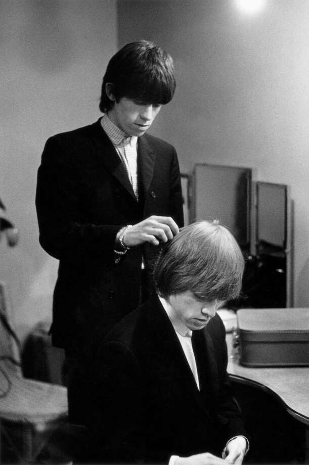 Keith Richards combing Brian Jones' hair as the Rolling Stones prepare backstage for a performance, 1964. Photo: Terry O'Neill, Getty Images / 1964 Getty Images