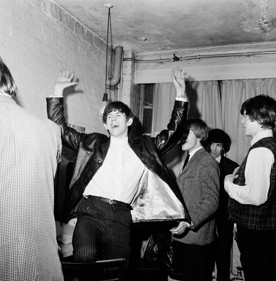 Guitarist Keith Richards laughing with Mick Jagger, Brian Jones and Bill Wyman backstage during an early Rolling Stones tour, December 1963. Photo: Chris Ware, Getty Images / 2006 Getty Images