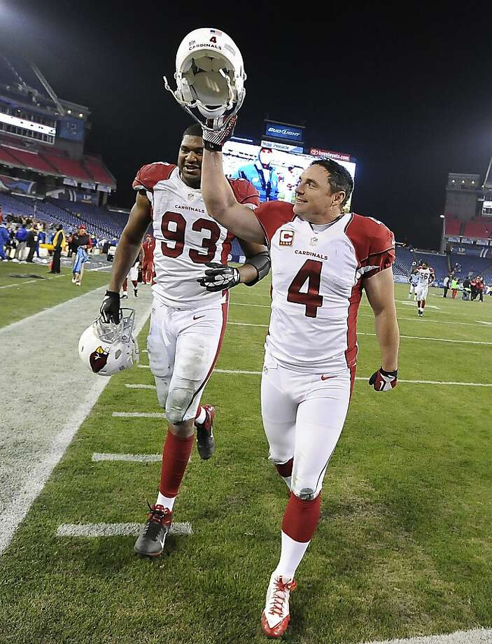After kicking the winning field goal, Arizona's Jay Feely leaves the field with defensive end Calais Campbell. Photo: Mark Zaleski, Associated Press