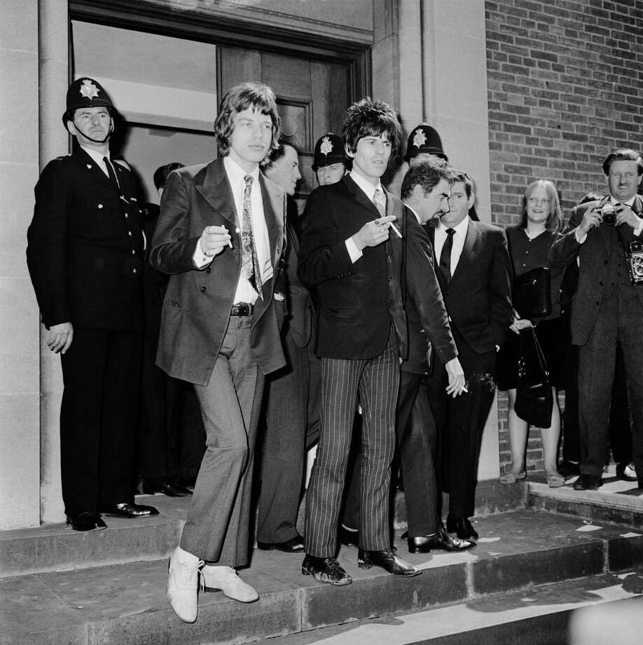 Singer Mick Jagger (left) and guitarist Keith Richards of British pop group The Rolling Stones outside Chichester Magistrates Court, where they are appearing with West End art gallery director Robert Fraser, accused of offences under the Dangerous Drugs Act. Photo: Ted West, Getty Images / Hulton Archive
