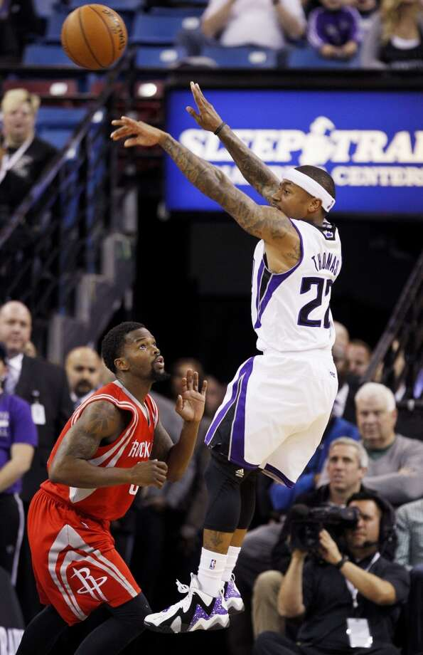 Kings point guard Isaiah Thomas (22) passes the ball around Rockets point guard Aaron Brooks. Photo: GENEVIEVE ROSS, Associated Press