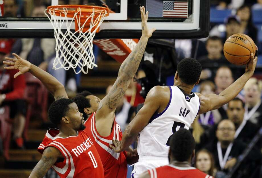 Kings forward Rudy Gay (8) scores around Rockets point guard Aaron Brooks (0) and Rockets forward Greg Smith. Photo: Genevieve Ross, Associated Press