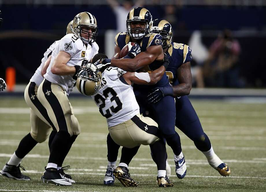 Pierre Thomas loses his helmet as he grabs Rams' Robert Quinn after Quinn's fumble recovery. Photo: Charles Rex Arbogast, Associated Press