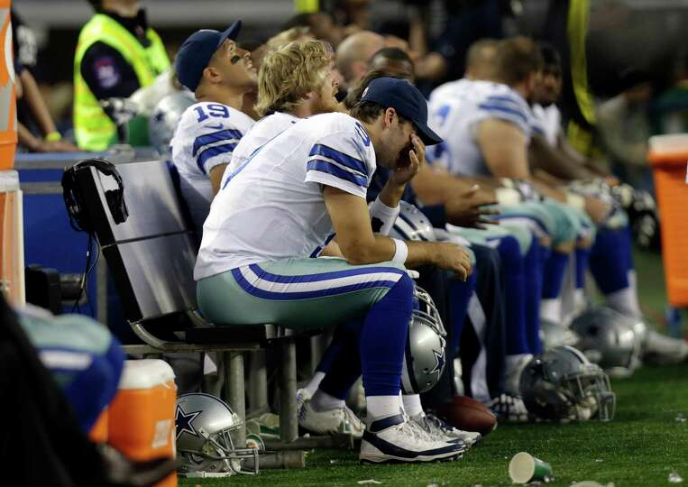 Dallas Cowboys quarterback Tony Romo (9) sits on the bench wiping his face in the final minutes of t