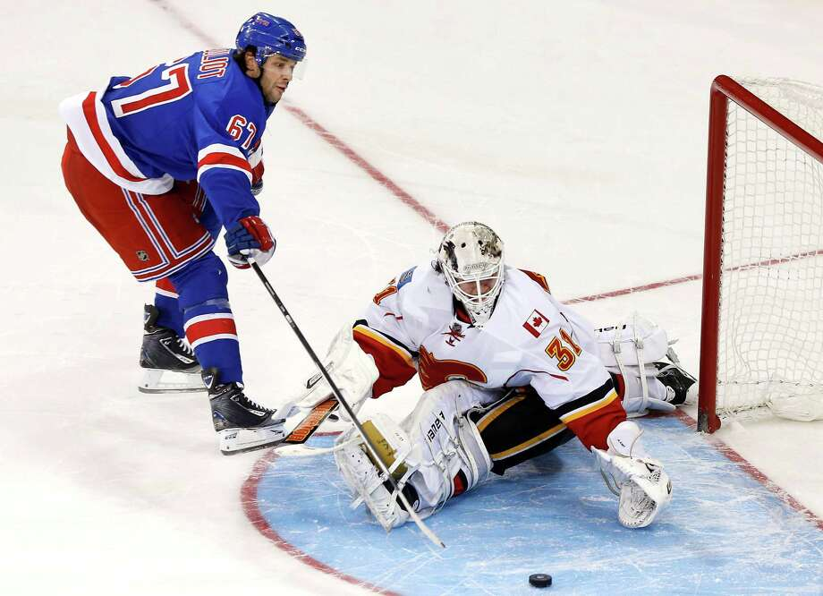 New York Rangers' Benoit Pouliot (67) scores the go-ahead goal against Calgary Flames goalie Karri Ramo, of Finland, during the shootout portion of an NHL hockey game Sunday, Dec. 15, 2013, in New York.  The Rangers won 4-3 in a shootout. (AP Photo/Jason DeCrow) ORG XMIT: NYJD110 Photo: Jason DeCrow / FR103966 AP