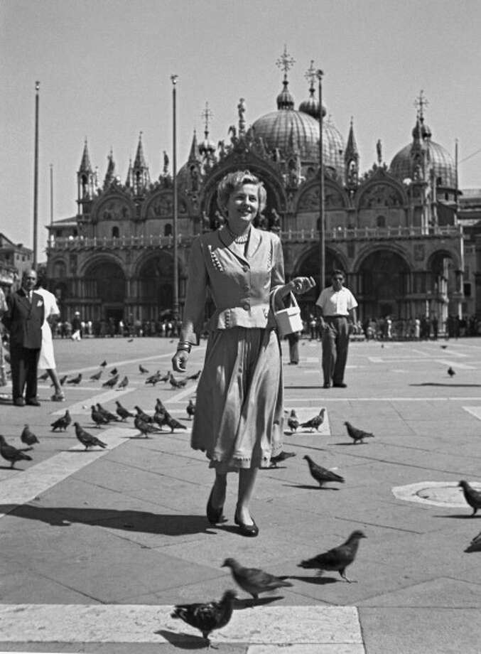 American actress Joan Fontaine wearing a tailleur, a pearl necklace and holding a handbag, walking in St Mark's Square surrounded by pigeons, the Basilica in the background, Venice 1949. (Photo by Archivio Cameraphoto Epoche/Getty Images) Photo: Archivio Cameraphoto Epoche / Hulton Archive