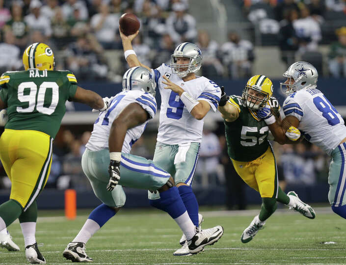 Dallas Cowboys quarterback Tony Romo (9) passes under pressure from Green Bay Packers outside lineba