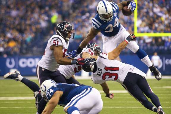 Colts running back Trent Richardson (34), who totaled 64 yards on 19 carries  Sunday,  hurdles Texans safety Shiloh Keo (31) during the third quarter at Lucas Oil Stadium.