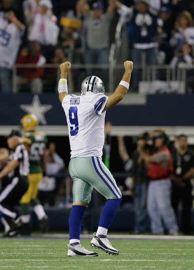 Dallas Cowboys quarterback Tony Romo (9) celebrates  a touchdown pass to teammate wide receiver Dez