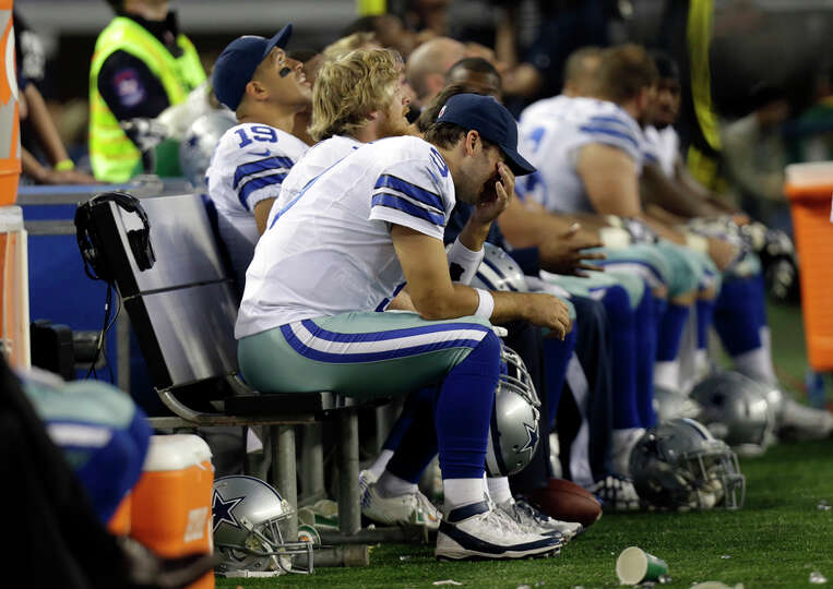 Dallas Cowboys quarterback Tony Romo (9) sits on the bench wiping his face in the final minutes o